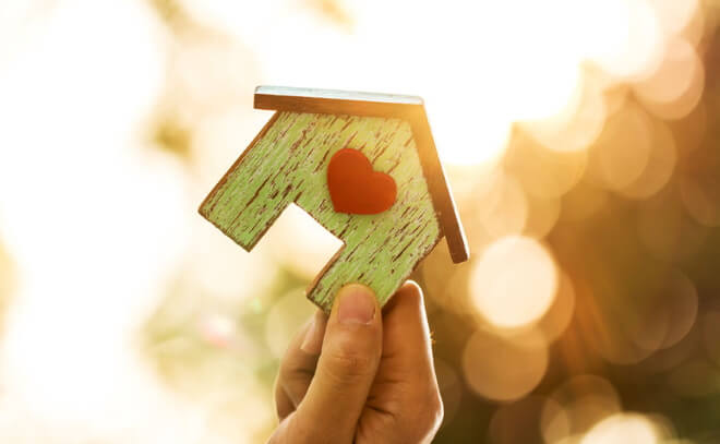 Women hand holding a home model with red heart