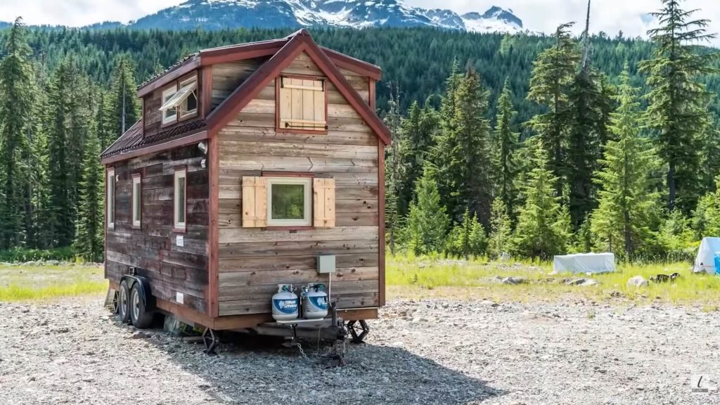 Beautiful tiny house surrounded with trees and mountain
