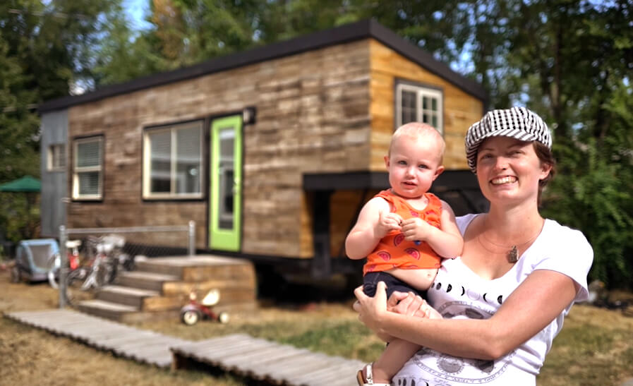 mother and toddler in front of a tiny home