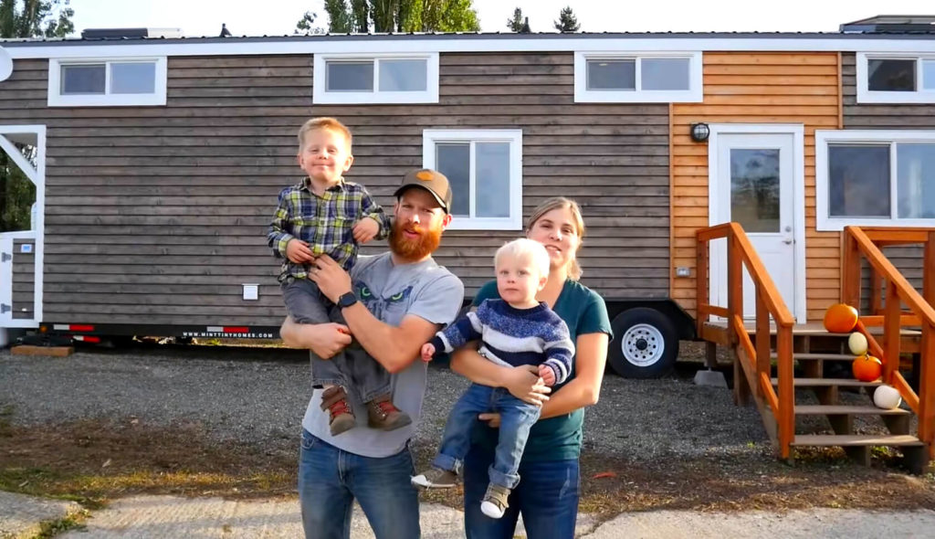a family of four in front of their house on wheels