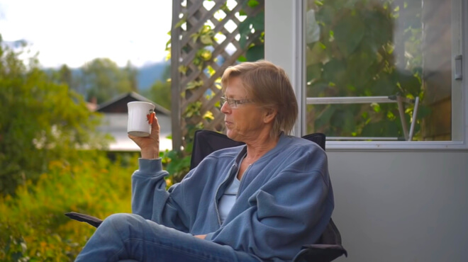 older woman sitting in front of a tiny house drinking coffee
