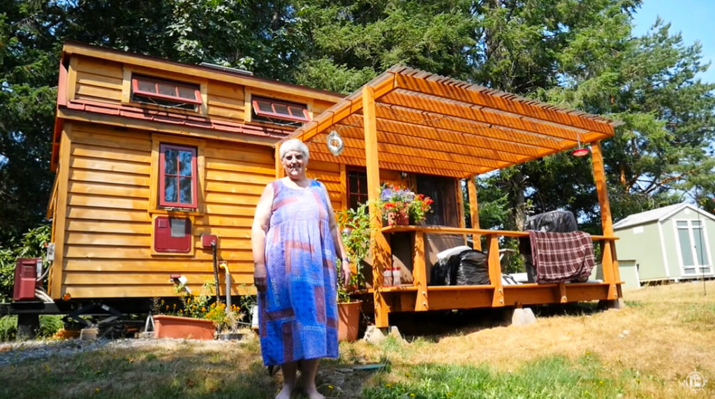 older lady standing in front of a tiny house